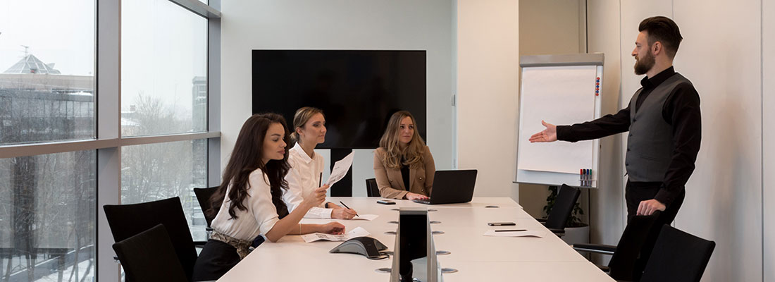 A man is presenting to three women around a large meeting table